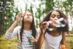 Two girls blowing bubbles in summer weather