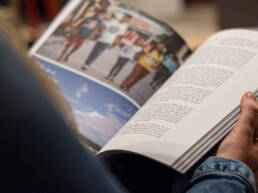 A woman holding a magazine, reading an article