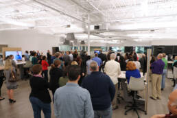 Employees and media at ribbon cutting ceremony for PTIC