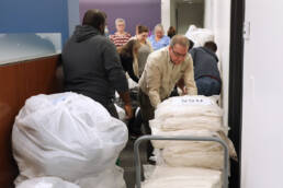 Photo of employees loading bags of blankets onto carts