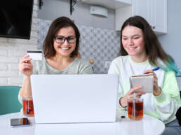 Family, mother and teenage daughter using laptop computer credit card and doing online shopping. Women sitting at home in kitchen talking smiling choosing gifts