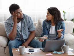 African American couple accounting family budget at home, wife scolding her husband for overspending and lack of money